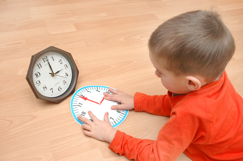 kisfiú tanulja az órát